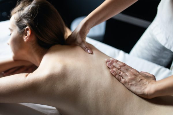 Young beautiful woman lying on massage table and enjoying massage