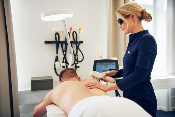 Clinic technician doing laser hair removal treatment on a client