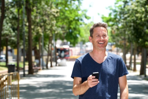 Older man standing outside with cellphone smiling on sidewalk