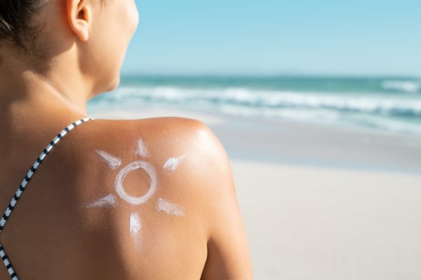 Woman with sun shaped sunscreen on shoulder