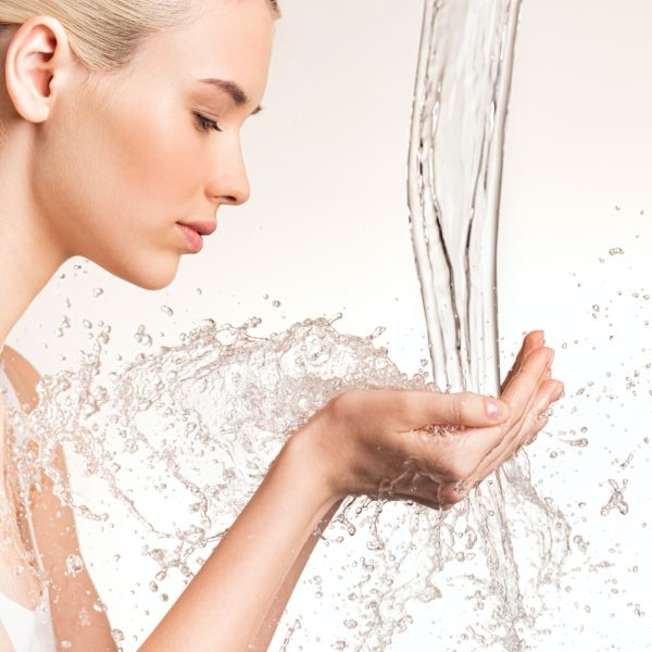 Photo of young woman with clean skin and splash of water.